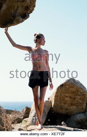 Woman standing on rocks at the beach - Stock Photo
