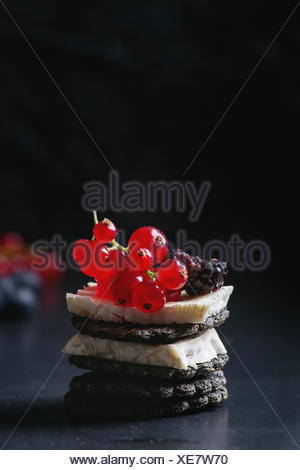 Black charcoal crackers with camembert brie cheese and berries blueberry, dewberry, red currant and sliced figs, served on vintage tray over dark meta - Stock Photo