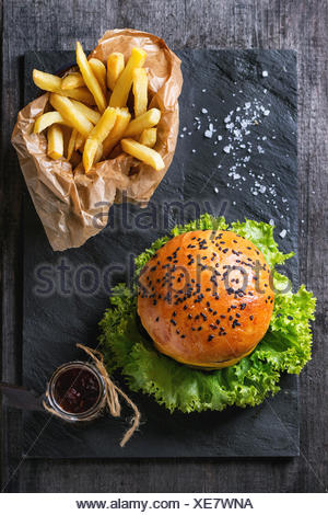 Fresh homemade hamburger with black sesame seeds and french fries potatoes in backing paper, served with ketchup sauce in glass - Stock Photo