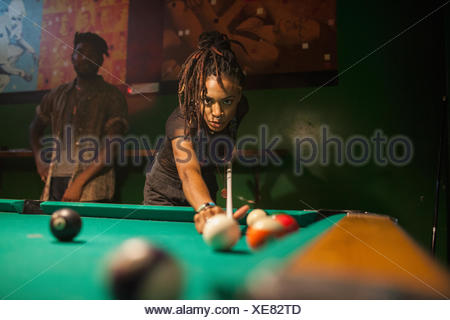 A young woman playing pool. - Stock Photo