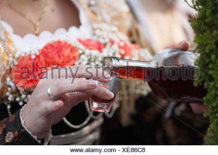 Woman pouring a shot of brandy, Leonhardi procession, Bad Toelz, Isarwinkel, Upper Bavaria, Bavaria, Germany, Europe - Stock Photo