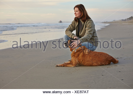Mature woman petting her dog on beach - Stock Photo