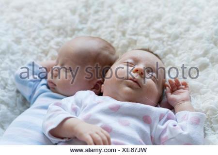 Portrait of sleeping newborn baby girl lying besides her twin brother - Stock Photo