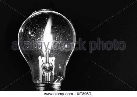 Close-Up Of Illuminated Electric Bulb Against Black Background - Stock Photo