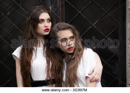 Two scared frightened horror girl in white dressing gown looking aside. Theme Halloween. Dark picture of two beautiful scared hiding girls with opened mouth on black window background. - Stock Photo