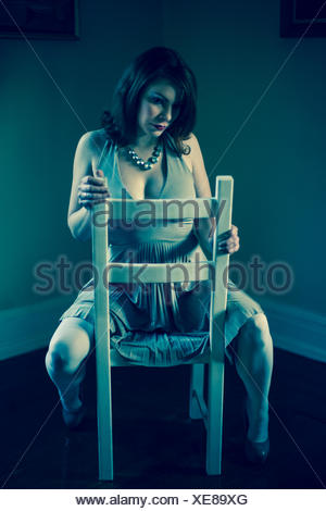 Portrait of mid adult woman, straddling chair - Stock Photo