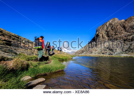 Hikers proceed on the shore of Lake Riffelsee with Matterhorn in the background Zermatt Canton of Valais Switzerland Europe - Stock Photo