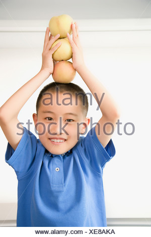 Portrait of a boy balancing apples on his head - Stock Photo