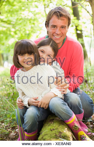 Father and daughters outdoors in woods sitting on log smiling - Stock Photo