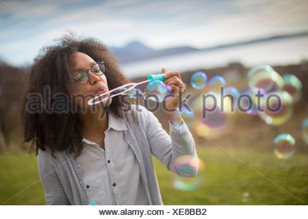 Mid adult woman blowing bubbles - Stock Photo