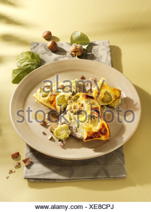 Brussels sprouts casserole with hazelnuts on an earthenware dish - Stock Photo