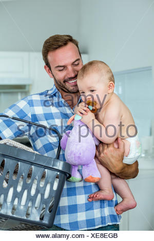 Father carrying playful son while holding basket in kitchen - Stock Photo