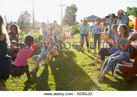 Neighbors cheering kids playing tug-of-war - Stock Photo
