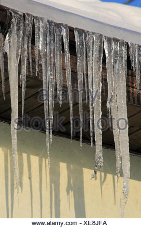 Icicles drooping from the roof - Stock Photo