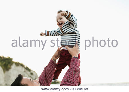 Father throwing smiling baby boy in air - Stock Photo