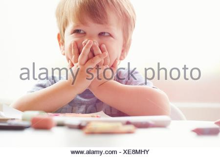 Boy sitting at table resting on elbows, covering mouth with hands, looking away - Stock Photo