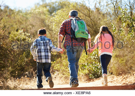 Rear View Of Father And Children Hiking In Countryside - Stock Photo