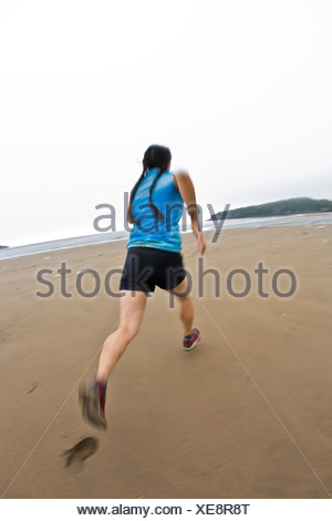 A young female running along the shores of the beach at Mispec Park, Saint John, New Brunswick, Canada. - Stock Photo