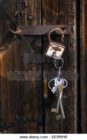 Close-up of barn door with padlock and bunch of keys hanging - Stock Photo