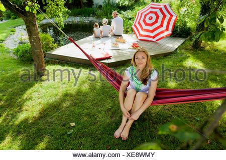 Woman sitting on hammock, family in background, Munich, Bavaria, Germany - Stock Photo
