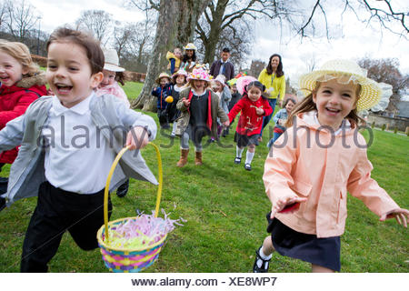 Nursery children running across a field during their outdoor Easter egg hunt, they are wearing handmade hats and carrying baskets. - Stock Photo