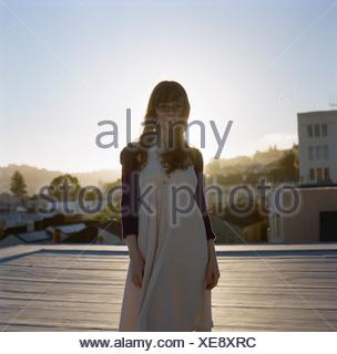 Portrait Of A Content Young Woman Standing Outdoors - Stock Photo