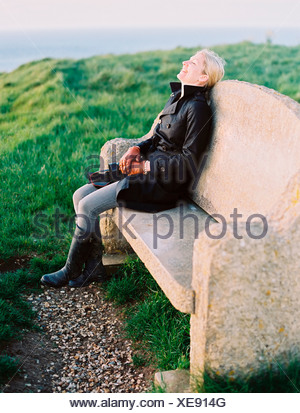 A woman seated on a stone bench on a coastal path. - Stock Photo