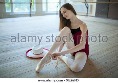 Young ballerina sitting on the floor dance classroom gently tyin - Stock Photo