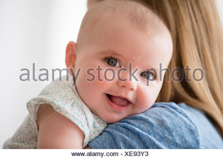 Portrait of baby girl (12-17 months) with mother - Stock Photo