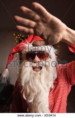 Man wearing Santa Claus hat and beard - Stock Photo