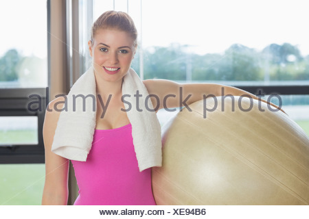 Fit beautiful woman carrying exercise ball - Stock Photo