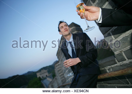 two businessmen holding wineglasses and talking on Great Wall,Beijing,China - Stock Photo