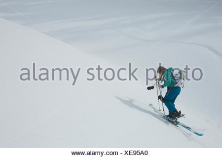 Teen girl skiing uphill with skins on her skis. - Stock Photo