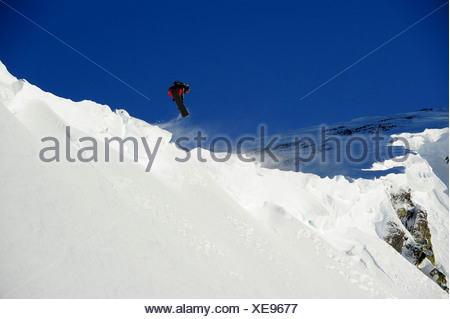A snowboarder catches air off a cornice in the Lake Tahoe backcountry, California. - Stock Photo