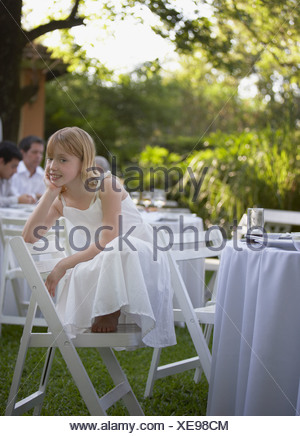 Young girl crouched on chair at outdoor party smiling - Stock Photo