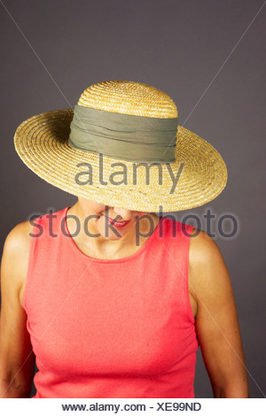 a woman summerly dressed wearing a strawhat - Stock Photo