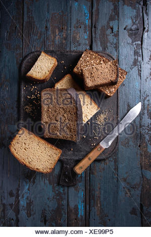 Variety loaves of sliced homemade rye bread whole grain and seeds with knife on black cutting board over old dark wooden background. Top view, space.  - Stock Photo