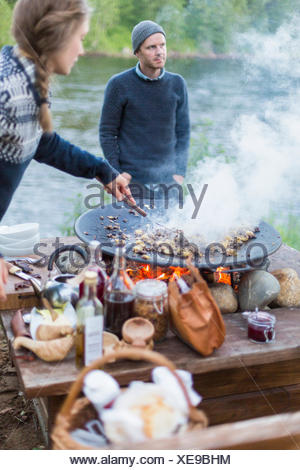 A woman cooking on a fire pit - Stock Photo