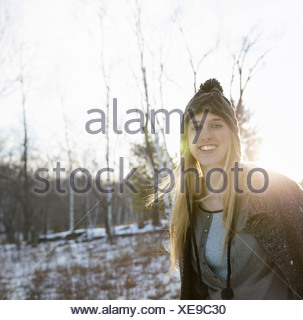 A young woman with blonde hair and a knitted woollen hat and coat Outdoors on a winter's day Snow on the ground - Stock Photo