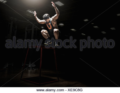 Young man leaping in gym - Stock Photo