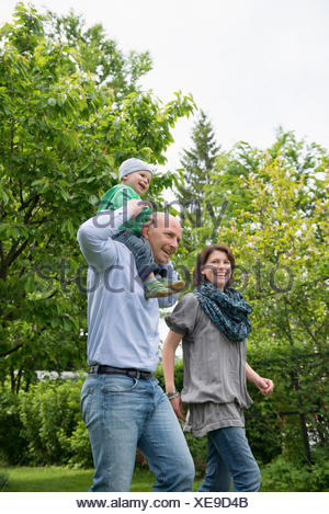Parents mother father baby piggyback garden - Stock Photo