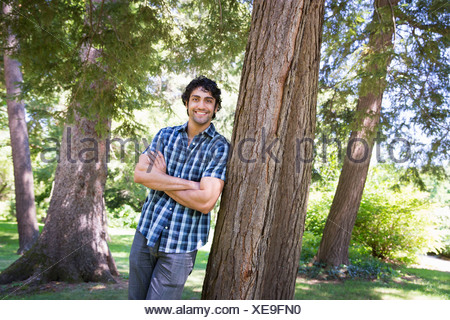 A farm growing and selling organic vegetables and fruit. A man leaning against a tree. - Stock Photo