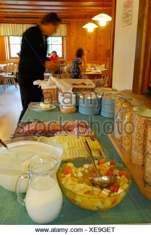 breakfast buffet with cereal and cold cuts, guests at tables out of focus in background, hut Franz-Senn-Huette, Stubaier Alpen r - Stock Photo