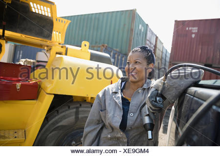 Portrait smiling female African American mechanic holding drill, fixing machinery in industrial container yard - Stock Photo