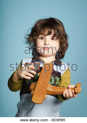 Little boy playing with toy airplane - Stock Photo