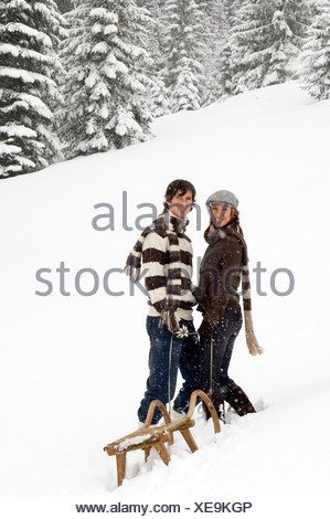 Austria, Salzburger Land, Altenmarkt, Young couple with a sled - Stock Photo