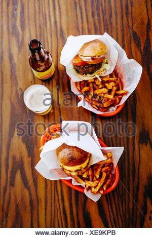 Directly above shot of fast foods served with beer on restaurant table - Stock Photo