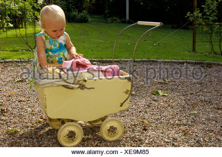 Little girl playing with a doll carriage in the park