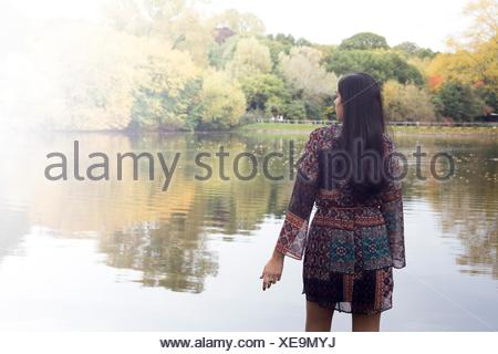 Back view of woman looking out at lake, Hampstead Heath, London - Stock Photo