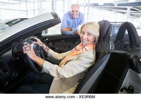 Portrait of smiling couple looking at convertible in car dealership showroom - Stock Photo